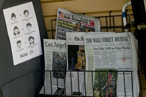 Newspapers for sale on a rack next to a sign exhorting people to wear a mask