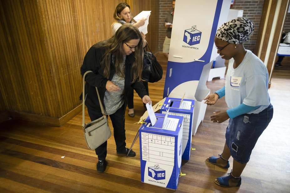 A woman puts her ballot paper in a ballot box during recent elections in South Africa