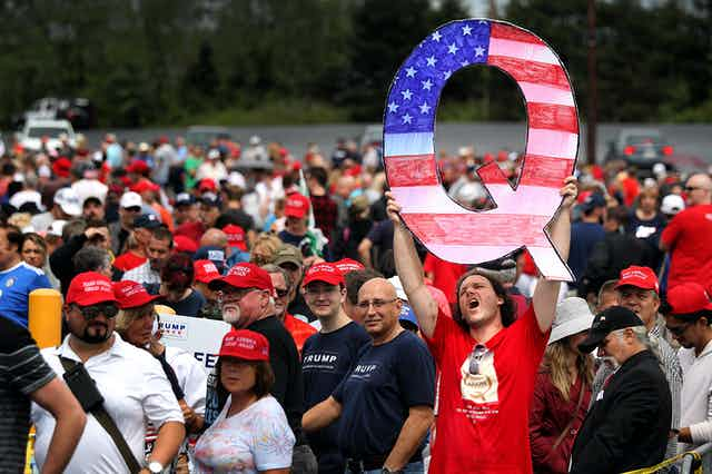 A man holds up a large 'Q' sign while waiting in line to see President Donald Trump at a rally.