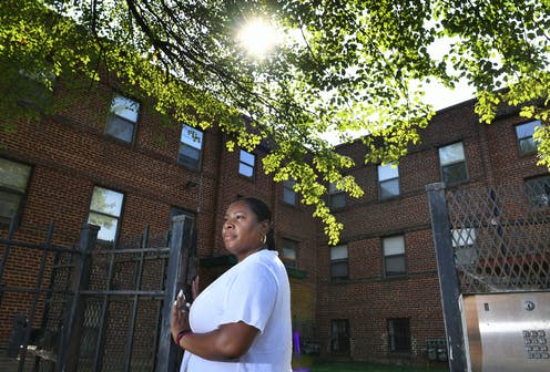 A Black woman stands at a gate to an apartment building.