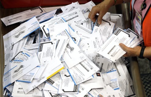 A person picks up mailed-in ballots from a large box of them.