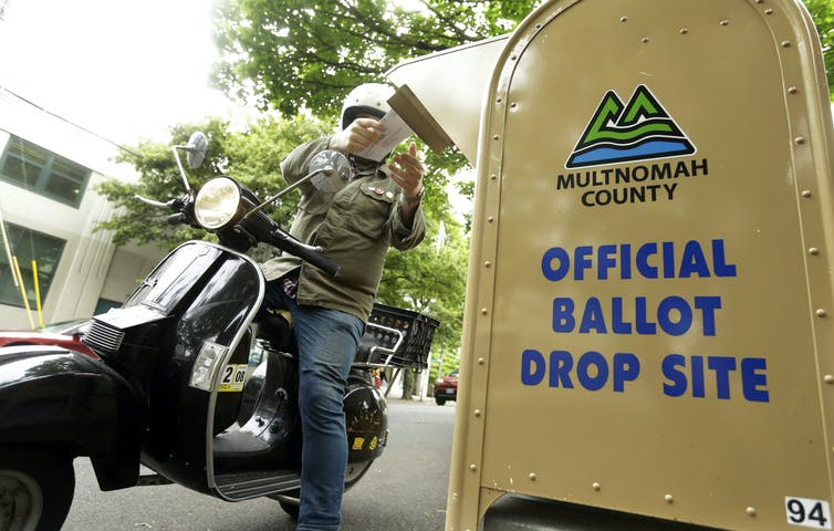 A motorcyclist puts a ballot in a drop box.