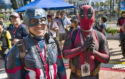 People dressed as Captain America and Deadpool stand in front of a crowd.