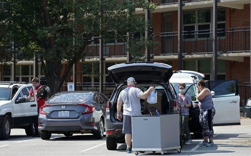 Parents help college students pack cars in a parking lot.