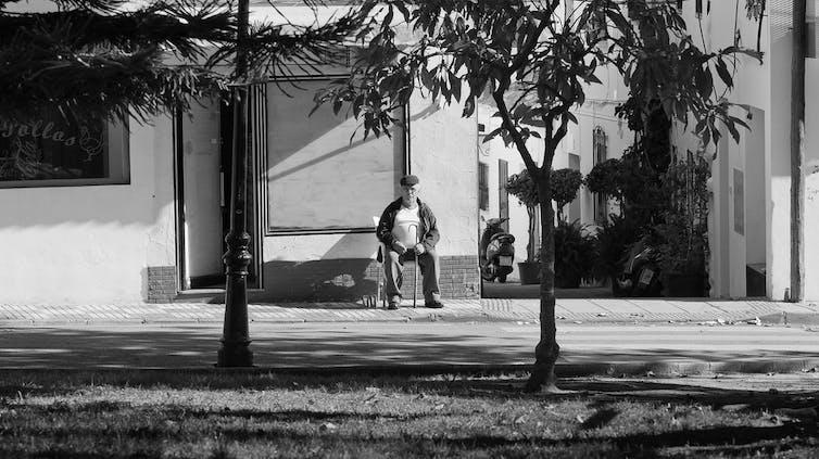Foto en blanco y negro de un hombre mayor sentado en una silla, en la acera de un barrio de casas blancas.