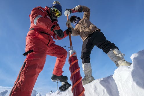 two scientists fully covered in cold weather clothing drill into the ice to extract an ice core. The photo is taken looking up at the two scientists and the photographer appears to be inside a pit dug into the ice.