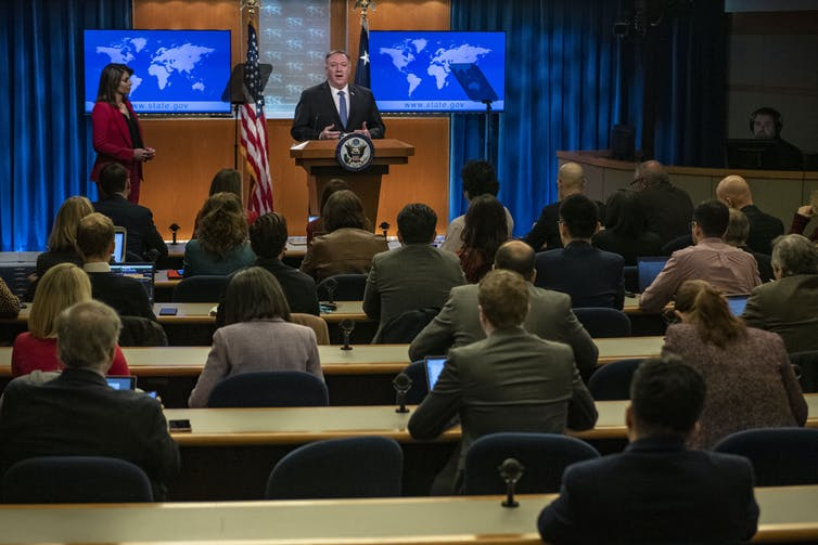 Pompeo, standing at the podium, speaks to seated reporters in the White House Press Briefing Room