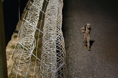 A uniformed soldier wearing a backpack walks next to the barbed wire fence surrounding Guantanamo Bay military base at night