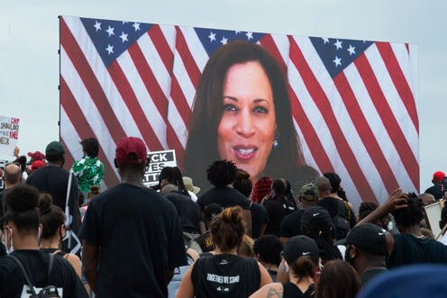 Kamala Harris speaking via a screen to demonstrators at the  protest against racism and police brutality.