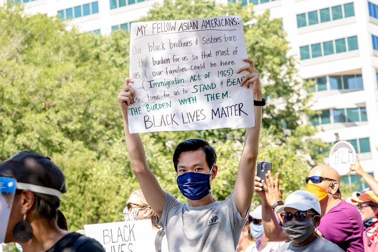 A young Asian man at a protest with a sign that says 'Black Lives Matter.'