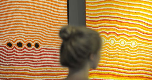A woman stands in front of two vibrant dot paintings