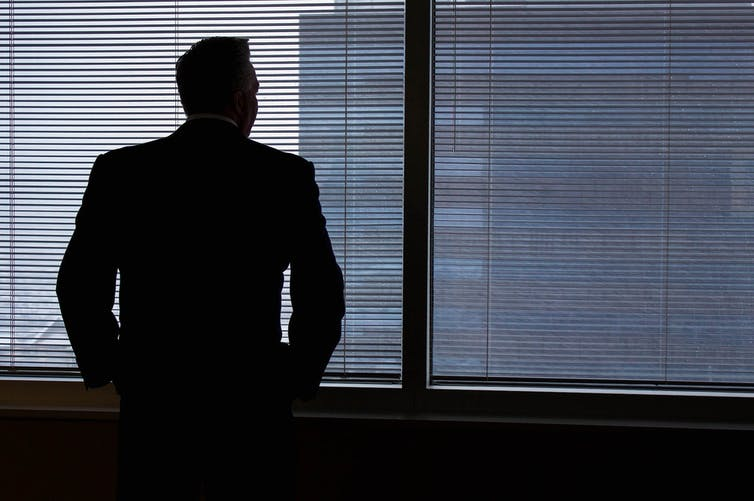 A man in silhouette in a suit stares out an office window.