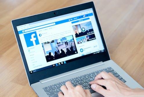 A laptop displays the Facebook platform.