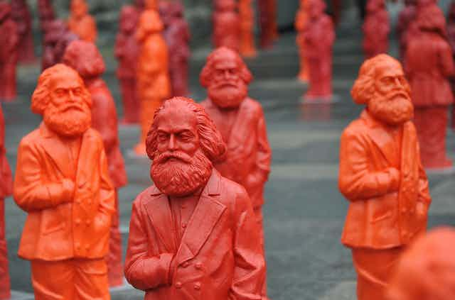 A crowd of red and orange plastic sculptures of Karl Marx