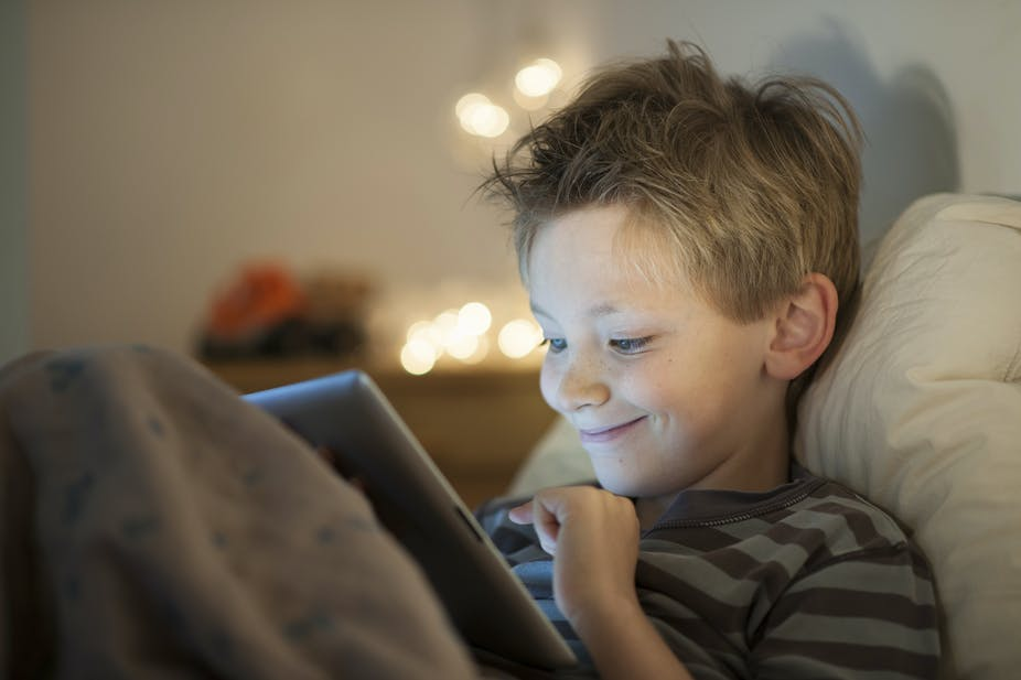 A young boy in bed and smiling while watching something on his iPad