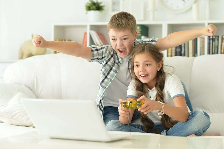 Boy and girl playing with a video game controller.