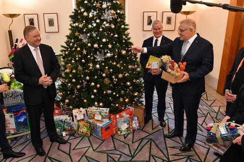 Anthony Albanese, Scott Morrison, and Michael McCormack, stand around a Christmas tree adorned in presents