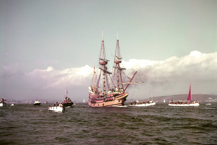 Replica of the Mayflower sailing surrounded by other smaller ships.