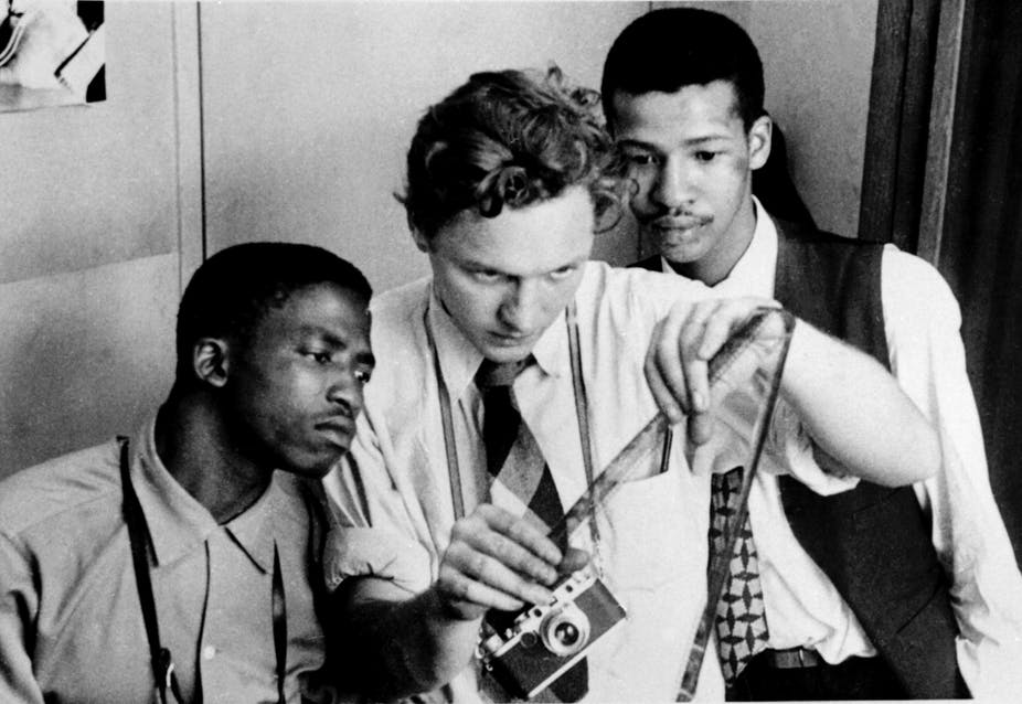 Three men in 1950s fashions examine a roll of film emerging from a camera.