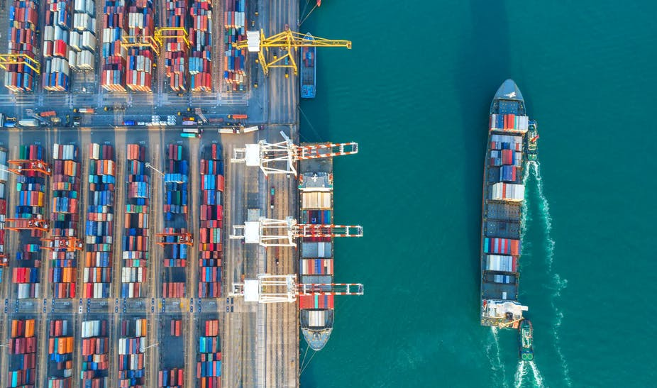 Shipping terminal with containers and cargo ships.