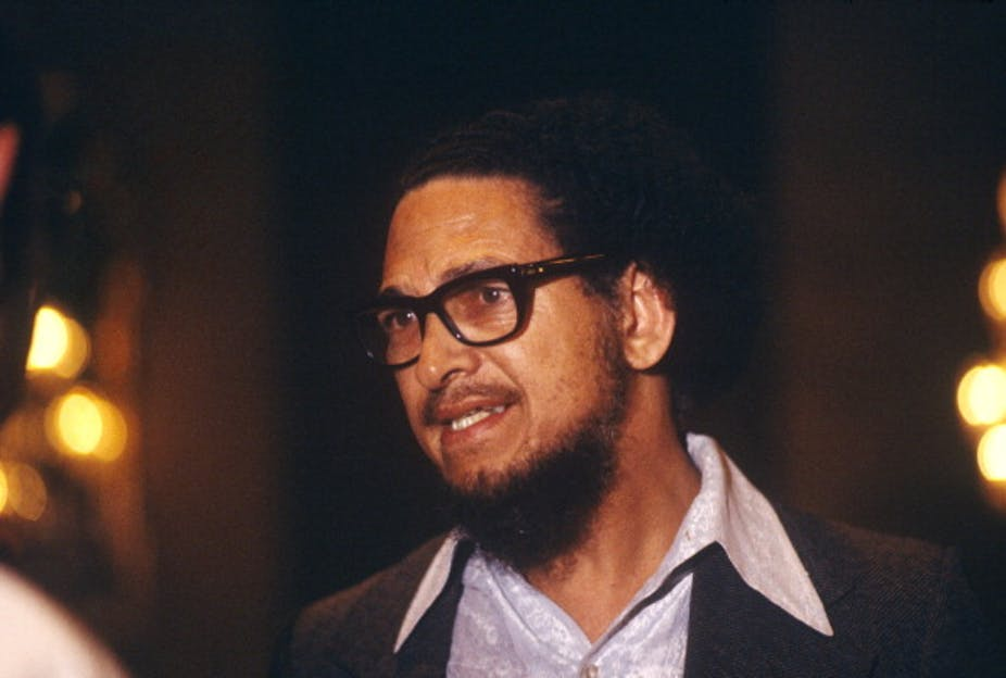 A bearded man with dreadlocks and heavy-framed spectacles gazes intently, looking ready to speak.