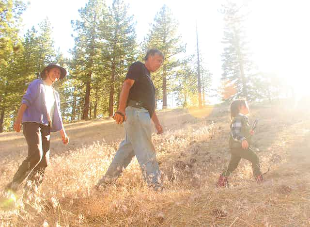 A grandchild walks across a tree-lined hill with grandparents in tow.
