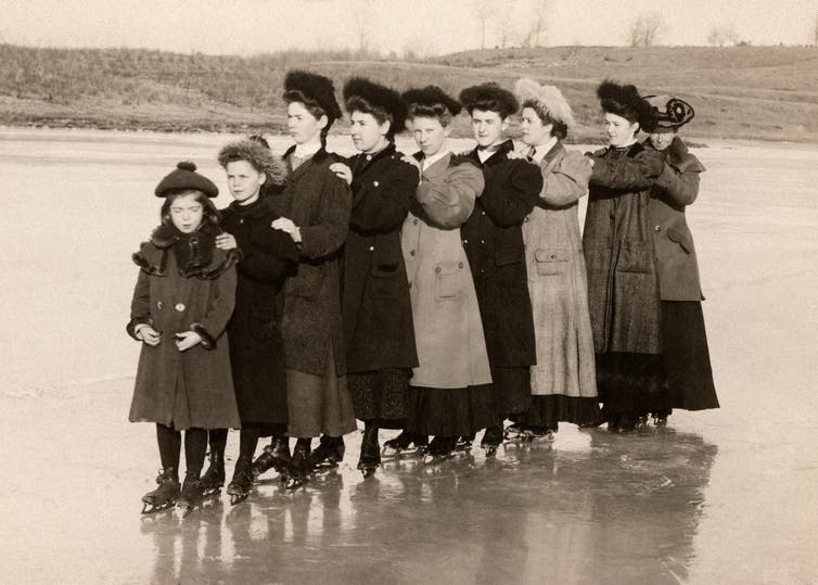 A line of Victorian women stand on a frozen lake.