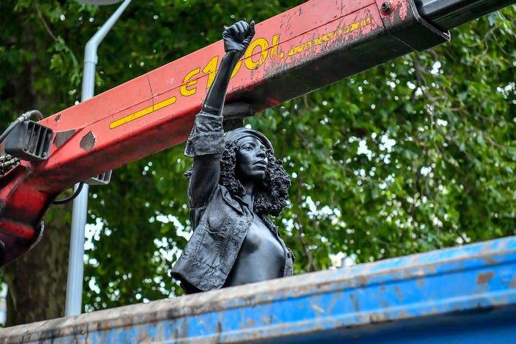 A sculpture of a woman protester rests in a waste skip, her fist in the air.