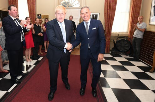 Boris Johnson shakes hands with his top civil servant.