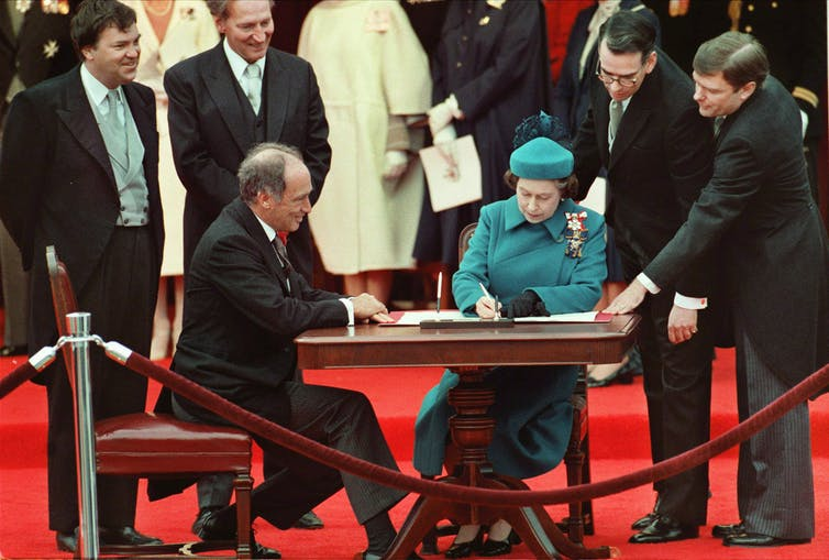 Pierre Trudeau sits at a desk on a red carpet looking on as Queen Elizabeth, in a teal suit, signs a proclamation.