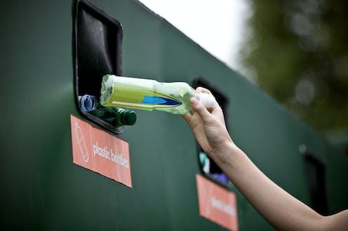 Someone depositing a plastic bottle in a bottle bank.