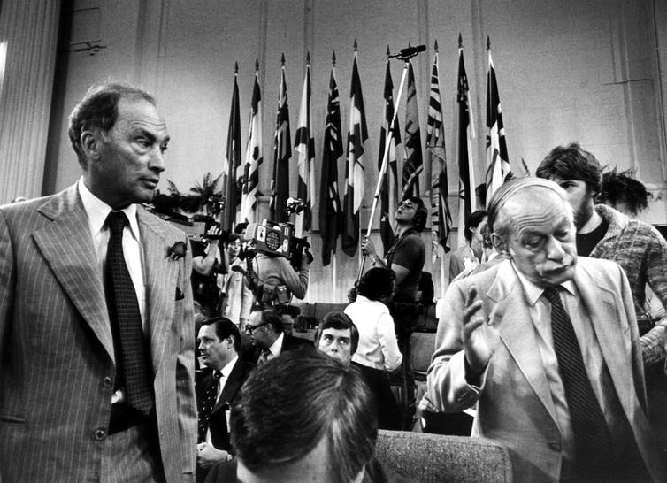 Rene Levesque, Québec premier, shrugs his shoulders and walks away from Pierre Trudeau at a conference with flags in the background.