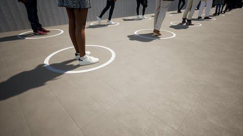 Alumnos en un patio sobre círculos blancos.