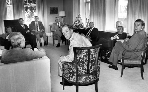 Pierre Trudeau turns in his seat to look at the camera as provincial premiers look on.