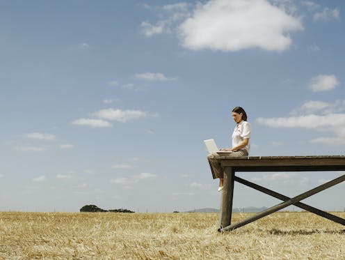A woman with a laptop on her lap sits on a wooden structure in an open field.