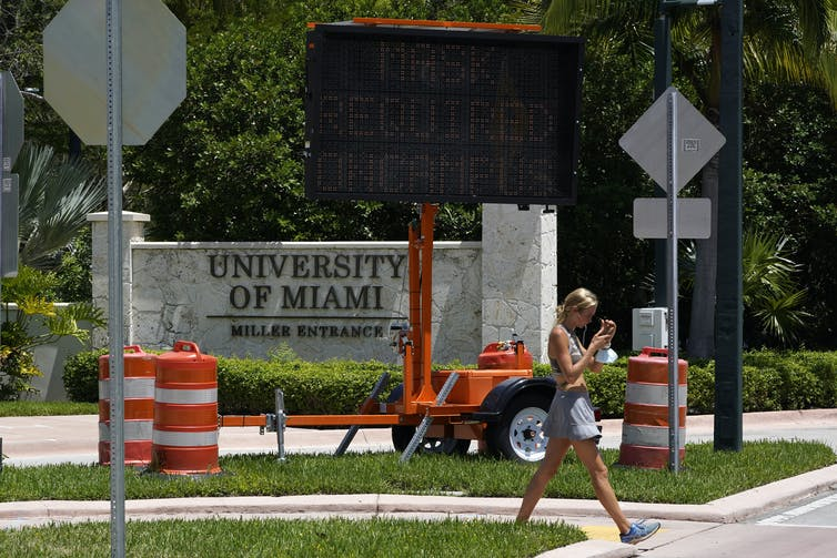 A female student walks in front of a sign at the University of Miami in Coral Gables, Fla.