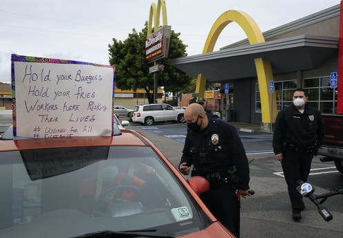 Los Angeles Police officers ask protesters in their vehicles to move along the drive-thru outside a McDonald's restaurant in the Crenshaw district of Los Angeles on April 6.