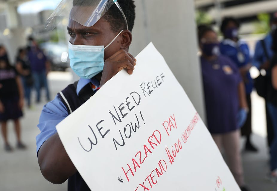 An unemployed airline worker holds a sign calling for an extension of federal benefits.