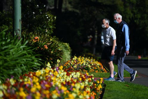 Two men wearing masks walk through Fitzroy Gardens in Melbourne on a sunny day.