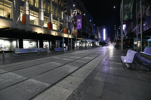 View of deserted Bourke Street Mall in Melbourne under nighttime COVID-19 curfew