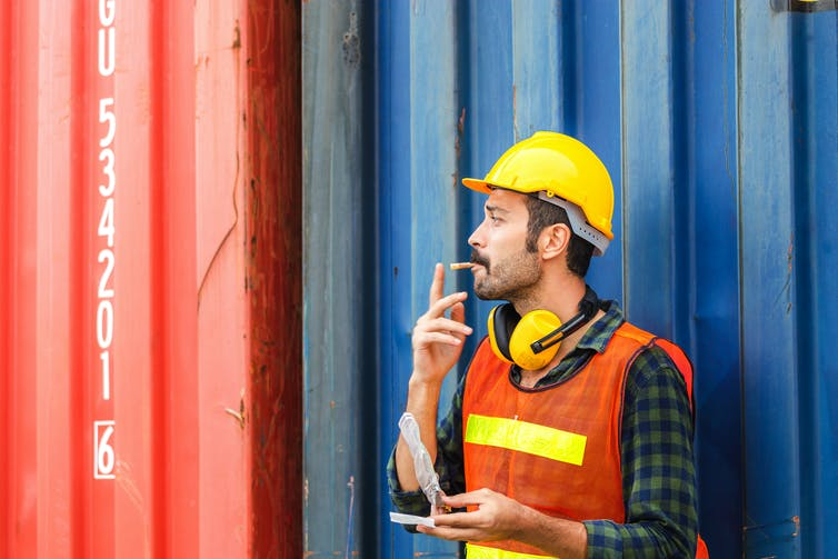 Worker in high-viz jacket and hard hat smoking as he leans against a shipping container