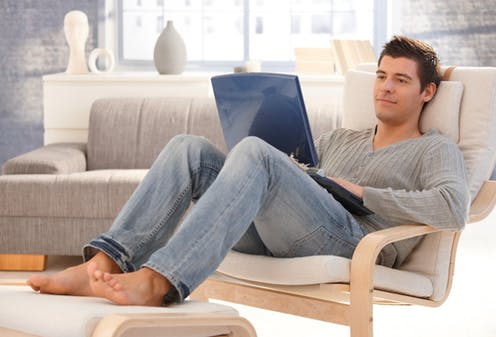 Man sitting in armchair looking at open laptop on his lap