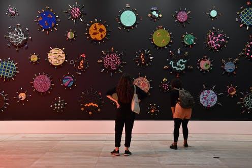 Two women stand in a gallery, looking at colourful shapes