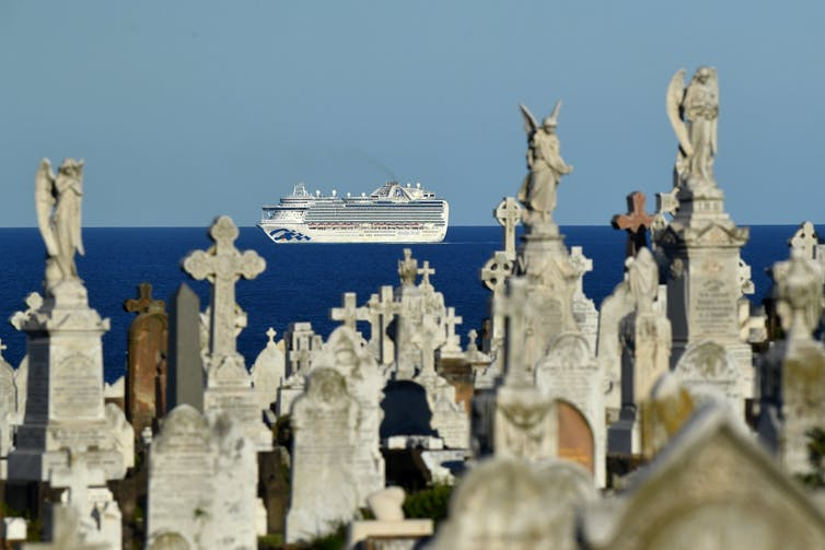 A cruise ship is seen at sea, framed by gravestones on land.