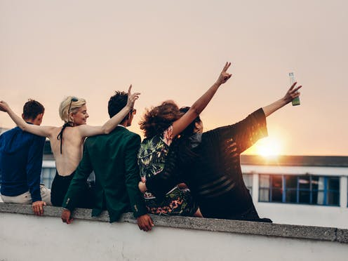 Five young people, with backs to camera, hugging, arms in the air, looking at the sunset