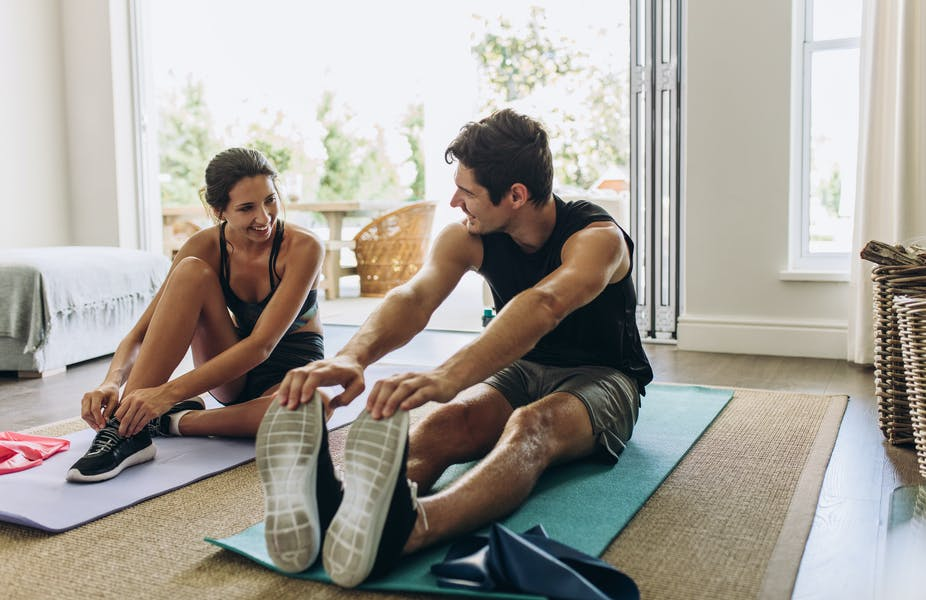 Young couple stretch after a workout.