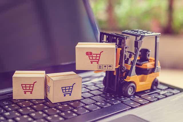 Una carretilla de juguete sobre un teclado de ordenador transporta paquetes ilustrados con carritos de la compra.