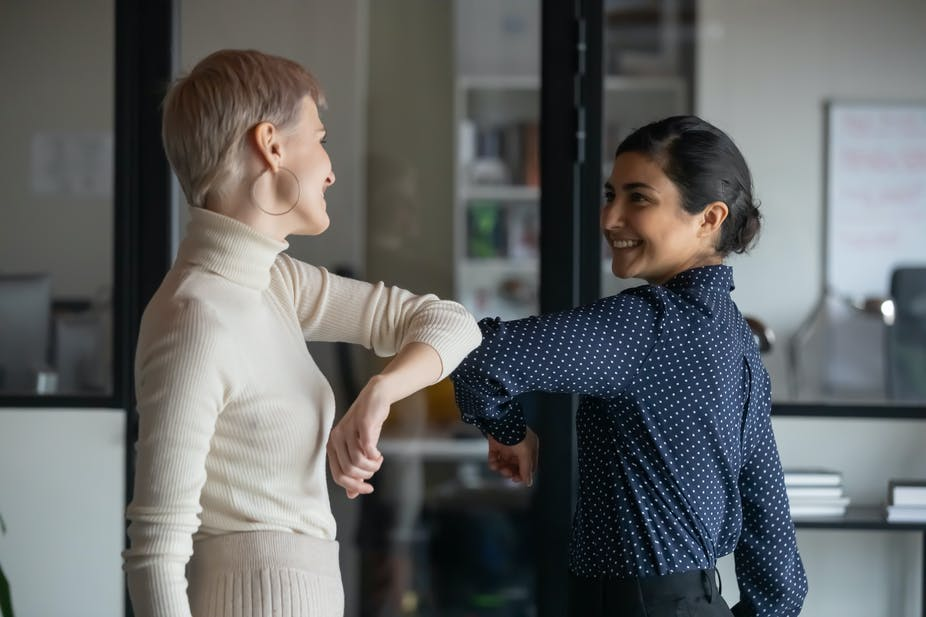 Two women touch elbows in the office.