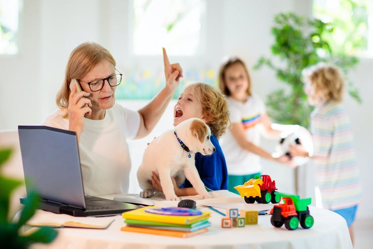 A white woman sits at a table in front of a laptop while she's on the phone and a child holds a puppy to her while two others fight over a toy in the background.