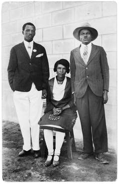 Two men stand and a woman sits between them on a chair, all in formal attire and looking at the camera unsmilingly.
